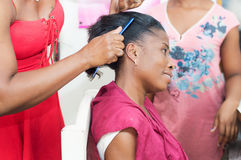 Straightening hair of the client. Royalty Free Stock Image