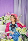 She straightens her hat surrounded by flowers. Girl straightens fashionable hat surrounded by flowers. The concept of innocent beauty Stock Image