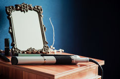 Straightner in front of old mirror. Photo of a straightener and makeup stuff in front of an old mirror Royalty Free Stock Photos