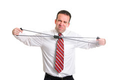 Strain. A young businessman straining to stretch a resistance band, isolated against a white background Stock Photography