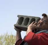 Strain. Bluecollar worker lifting a heavy cinder block Stock Images