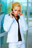 Strained business woman talking on mobile. Strained modern business woman talking on mobile at office building Stock Image