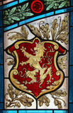 Strained-glass Window - Lion Banner Sigil. A lion shaped banner / sigil on a strained-glass window, similar to the sigil of House Lannister in Game of Thrones / Stock Photos