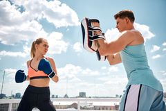 Strained woman is boxing with trainer on rooftop royalty free stock photo