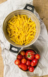 Strainer full of Italian pasta and a cup full of tomatoes on a paper and canvas Stock Image