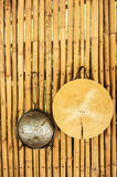 Strainer and wooden cutting board. Hanging on a bamboo wall in an outdoor kitchen royalty free stock photography