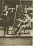 the strains of the itinerant harpist come through the din of traffic Stock Images