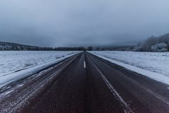 Strait road with snowy fields on both sides. Strait road with snowy white fields on both sides Stock Image