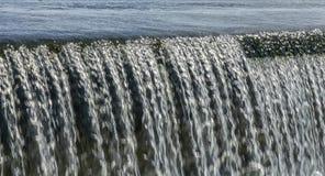 Stralen die van water over de dam vallen stock afbeelding