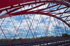 Stralen van een rood overspannen brugclose-up tegen een blauwe hemel textuur van het rooster van de delen van de staalbrug bebouw stock foto