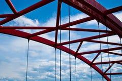 Stralen van een rood overspannen brugclose-up tegen een blauwe hemel textuur van het rooster van de delen van de staalbrug bebouw royalty-vrije stock foto's