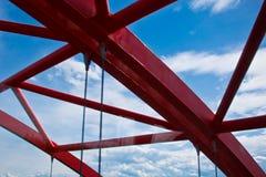 Stralen van een rood overspannen brugclose-up tegen een blauwe hemel textuur van het rooster van de delen van de staalbrug bebouw stock afbeelding