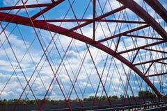 Stralen van een rood overspannen brugclose-up tegen een blauwe hemel textuur van het rooster van de delen van de staalbrug bebouw stock foto's