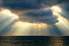 Stralen van zonlichtstralen die door dramatische wolken op het overzees in stralen van licht glanzen stock foto's