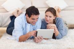 Stralend paar dat een tabletcomputer met behulp van Stock Fotografie