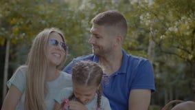 Stralende familie met dochter het ontspannen in park stock videobeelden