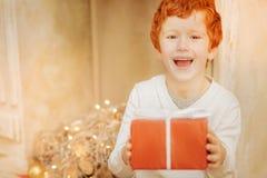 Stralende jongen worden die die over aanwezige Kerstmis wordt opgewekt stock fotografie