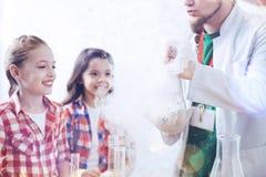 Stralende schoolmeisjes die die fuming fles bekijken door chemieleraar wordt gehouden royalty-vrije stock foto's