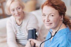 Stralende vrouwelijke arts die met sphygmomanometer in camera glimlachen stock afbeeldingen