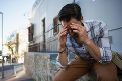Stramad åt ung man med huvudet i händer som sitter på behållande vägg Royaltyfri Fotografi