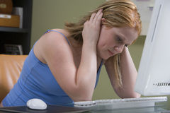 Stramat åt kvinnasammanträde på datorskrivbordet Arkivfoto