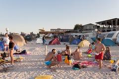 Strandüberblick - Touristen, welche die letzten Strahlen der Sonne genießen Stockbilder