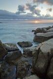 strand över stenig solnedgång Arkivfoto