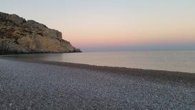 strand över stenig solnedgång Arkivbild