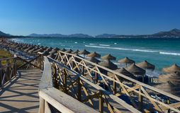 Strand av majorcaen med en träbro och montains Arkivbild