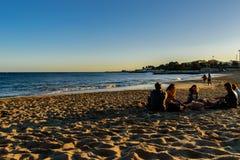Strand av Santo Amaro de Oeiras - 10 mars 2019 - grupp av vänner som tillsammans bor i den sena eftermiddagen som sitter på sande royaltyfria bilder