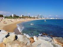 Strand in Barcelona met blauwe overzees en rotsen Stock Foto