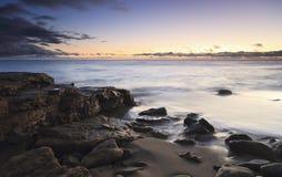 Strand bij schemer stock afbeeldingen