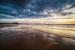 Strand bij zonsondergang in een stormachtige dag Royalty-vrije Stock Foto