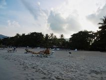 strand bij zonsondergang met sommige mensen stock afbeeldingen