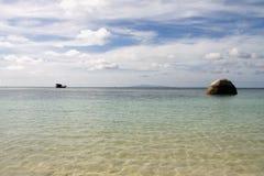 Strand, Boot und ein Felsen Stockfotos