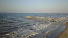 Strand de kust kustNoord-Carolina van de visserijpijler holden golven lopend op strand stock footage