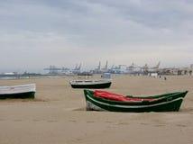 Strand in de winter met boten op het zand met in afstandskranen van een scheepswerf aan Valencia in Spanje Stock Foto's