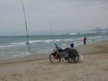Strand in de winter met een zittingsman daarna zijn fiets en lopende vrouwen met in afstand een scheepswerf aan Valencia in Spanj stock afbeeldingen