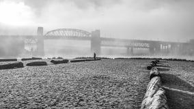 Strand en brug in de mist Royalty-vrije Stock Foto's