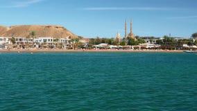 Strand en toeristen bij de toevlucht dichtbij het mooie overzees in de zomer op een zonnige dag Tegen de achtergrond van palmen stock footage