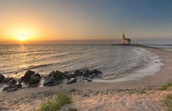 Strand en vuurtoren in zonsondergangkleuren stock afbeelding