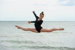 Strand för gymnastdansareJumping On The hav Royaltyfri Foto