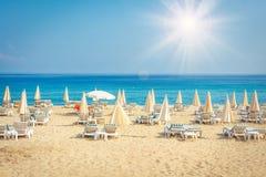 Strand för semesterorthotell på havet Sommarsemester på den tropiska stranden Sunbeds och paraplyer på havsstranden Royaltyfri Fotografi