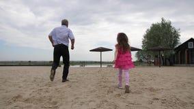 Strand Farfar- och sondotterkörning tillbaka till kameran De spelar på stranden nära vattnet 4K l?ngsam mo stock video