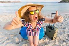 Strand, Feiertag, Ferien und Glück-Konzept - junge lächelnde Frau nahe dem Meer mit ihrem Gepäck, das sich Daumen zeigt Lizenzfreie Stockbilder
