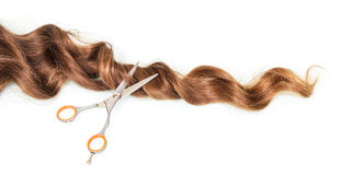 Strand of female wavy hair and scissors isolated on white Royalty Free Stock Photos