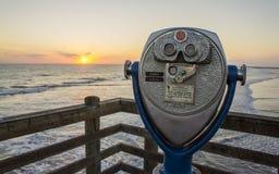 Strand-Ferngläser und Sonnenuntergang am Ozeanufer-Pier stockbild