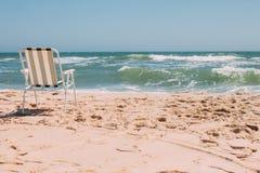 Strand-Frühlingsmeer des Klappstuhls alleinmit Wellen lizenzfreies stockbild