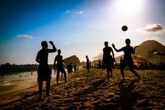 Strand-Fußball durch Sonnenuntergang stockbilder