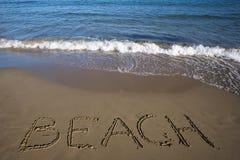 Strand geschrieben auf nassen Sand Lizenzfreies Stockfoto